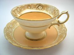 Beautiful tea cup and saucer made by Hammersley England Peach and offwhite set with gold filigree, The backstamp date this tea cup 1939+ The tea cup is 2 1/2 high and the saucer is 5 1/2 diameter The rims are gilt. It is in a very good condition, no chips, no hairline and no gold