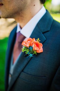 Unique and colorful boutonniere with roses, thistle, and seeded eucalyptus.