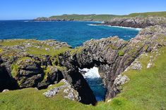 A view from the south western side of the Rhinns of Islay, the natural arch near Port Fròige with Lossit Bay in the background. The beach and dunes at Lossit Bay are hidden from view by the cliffs … Isle Of Islay, Outer Hebrides, Scottish Islands, Scotland Travel, Britain, Beautiful Places, Scenery, Landscape, Arch
