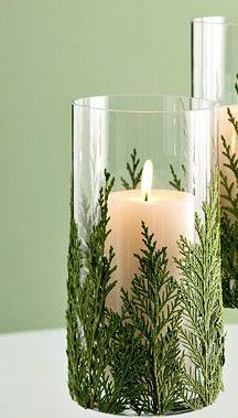Christmas candle decoration. As simple as a wide glass, arizona cypress leaves and a white candle.