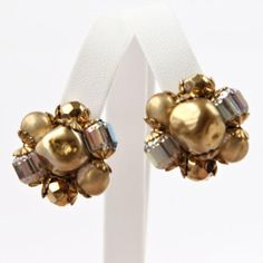 Vintage bead cluster clip earrings have centers of large baroque imitation pearls in the center, surrounded by smaller beads of matte goldtone, iridescent faceted cylinders and faceted goldtone rounds. To learn more, or to purchase, please visit our we...