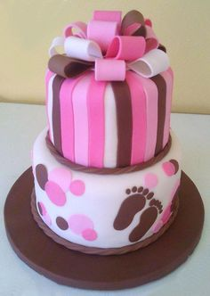 A baby shower cake in brown and two shades of pink with a fondant and sugar paste edible bow in complimentary colors on top.  Created by Sweet Pea Cake Co. in Colorado Springs.