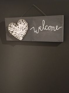 Leuk welkom bord op basis van hout, greywash, spijkers, lint en een krijtbordstift!