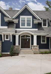 Navy siding, white trim, cedar posts, limestone rock, cedar shutters, silver/galvanized metal roof