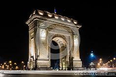 A long exposure night shot of the Arch of Triumph in Bucharest showing the night traffic around the emblematic building