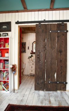 Old wood doors on a sliding rail system! I would so love this in my house!!