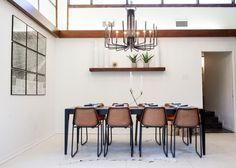 Eames inspired molded chairs with metal bases, a simple unadorned dining table and visually striking chandelier help define the new dining space.