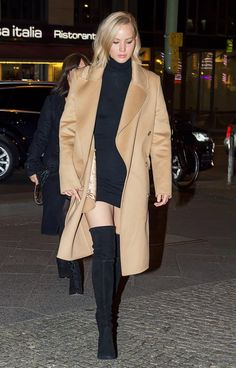 Jennifer Lawrence wears a black dress and camel coat with black suede over-the-knee boots.