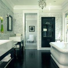 Master bathroom retreat, great curve on the tub, contrasting colors, chandelier, spa-like.