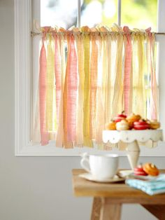 Decorating with ribbon. I'm not really a frilly girly-girl, but I like the idea of the sheer fabric strip/ribbon cafe curtain and the ribbon woven over a chair cushion.