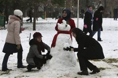 Iranian women build a snowman at the Laleh Park in central Tehran, Iran, Sunday, Jan. 16, 2011, as snow forced authorities to close city schools on Sunday