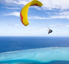 Paraglider Gavin McClurg hangs over incredible tropical lagoon in Huahine, French Polynesia