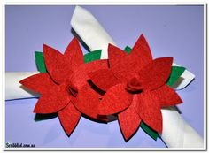 This is a beautiful napkin holder for Christmas. These felt Poinsettia napkin holders are a fantastic way to add a special touch to your Christmas table setting. In fact if you simply change the flower color this craft can suit many occasions. What you will need...Red and Green felt, scissors, a napkin, a Poinsettia template. Step One...Cut out the pieces from your template. Step Two...Place your template pieces on your felt, Cut out one red 'bone' shape, two red flower shapes and one green…