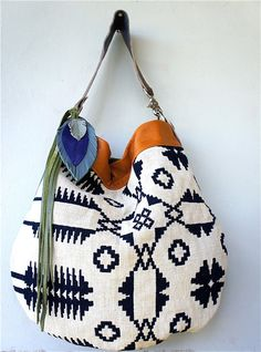Printed canvas hobo with leather feathers and trim.