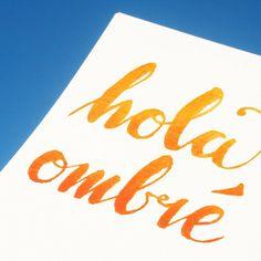"""hola ombré"" set against today's stunning blue sky #watercolourtypography #brushlettering #istilllovecaligraphy #handlettering #handtype #welovetype #thedailytype #handmadefont #ombretype @rebeccafeinerdesign"