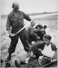 """Tacloban Air Field, Leyte, Philippines, Oct 20, 1944: Original caption: """"Wounded tankers of Sixth Army, X Corps, 1st Cavalry Division, 2nd Brigade, 7th Calvary Regiment, 1st Squadron, receive first aid from a corpsman after their M4 Sherman medium tank hit a mine at the edge of Tacloban Air Field."""""""