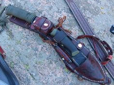 kukri sheath. Carries backup knife and sheath, water tabs, mini fishing kit, flashlight, ferrocerium flint, petroleum jelly cotton balls, 550 cord and wrist strap and the back is inscribed with a basic star chart.