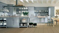 Cucina in stile country chic con penisola, finitura Azzurro Aurora. Tavolo English Mood quadrato e sedie Lynton.