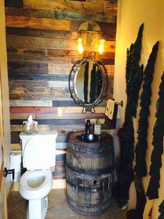 A bathroom remodel I did using upcycled pallet wood, a whiskey barrel, reused parts of the barrel I cut out to make the light fixture. Black pipe for the towel and toilet paper holders as well as a handicap bar. The trees on the right are hand carved from pine. The top of the barrel is covered with pennies and covered with epoxy.
