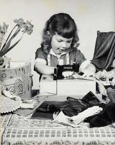 1960 Black and white photograph of little girl sewing on her old mini Singer sewing machine. Look at that concentration! YES>>>THAT COULD HAVE BEEN ME