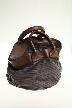 Small bag with two handles completely hand-stitched, made in fine soft leather, dyed thoroughly.