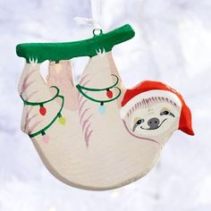 This hanging sloth ornament is features a Santa hat-wearing sloth tangled in Christmas lights. A delightful addition to any Christmas tree or holiday decoration! <br><br>Paper Source Exclusive.