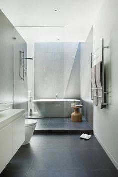 carrelage gris anthracite, baignoire ovale et porte serviettes mural
