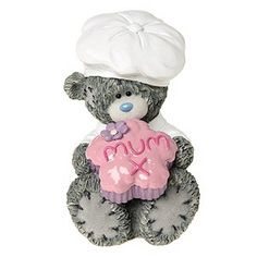 """A charming Me To You collectible especially for Mums. Features the adorable blue nosed bear donning a chef's hat and presenting an iced pink flower shaped cup cake with """"Mum x"""" iced on. A lovely gift for your special Mum."""