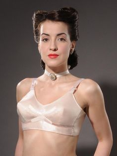 This stunning bra gives an authentic 1940s shape to the bust – somewhat pointy, but not nearly so much as a bullet bra.    A lot of our customers are 1940s fashion enthusiasts, but because bra design was really in its infancy then, it was rather hard for us to produce an period perfect Forties bra that would stand up to modern requirements of fit and comfort.    Although bras were first introduced in the early 20th Century, it wasn't until the late 1930s that the concept of cup sizes was…