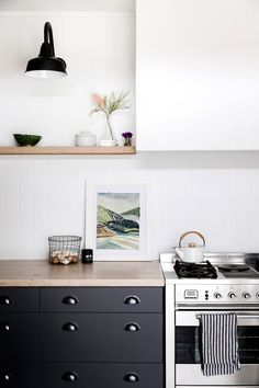 Dark cabinetry, light wooden worktop, white walls, black sconce