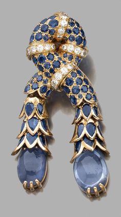 René BOIVIN 1955 , Broche clip 'nœud de passementerie' en or jaune, constituée d'une cordelière pavée de saphirs ronds facettés en serti à grains, coupée de quatre liens sertis de diamants taille brillant en ligne.