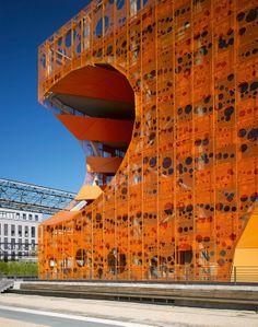 """Офисный центр """"Оранжевый куб"""" в Лионе, 2010. """"Дырка"""" позволила сделать защищенные от дождя и ветра балконы, а перфорированный фасад из тонко..."""