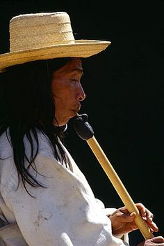 COLOMBIA General Kogi man playing flute. Kogi flute resembles a huge matchstick