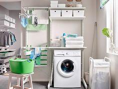 Wasruimte met een opbergoplossing die gaat van vloer tot plafond uitgerust met droogrekken en planken, met daarvoor een waszak op wielen