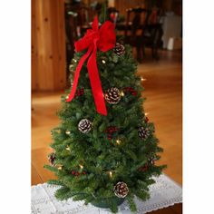 Made in Maine with fragrant balsam greens and decorated with real pinecones, lifelike holly berries, and a hand-tied red velveteen; bow tree stablizer for proper shipment and inserted in a plastic bag for freshness. The sparkle of the white holiday lights illuminates the holiday season.