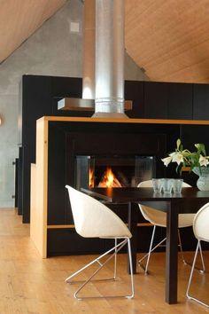 Det svarte spisebordet matcher peisen og skapveggen. Stolen «Pop Corn» er en 50-tallsklassiker.