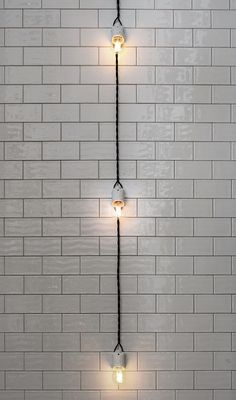 A string of lights against white subway tile at Restaurant Museet in Stockholm