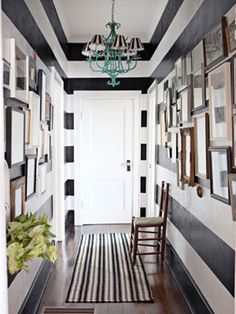 The striped entry way combined with the gallery walls is a very cool idea for adding maximum style to a small space. #stripes #entryway #gallerywall