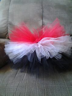This tutu skirt in red, white and black is stacked with different lengths of layers.  This was created  by Angie at Tutus 2 You www.facebook.com/... or email tutu2you1@gmail.com