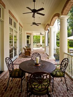 White columns and contrasting brick floor and accents are all the decoration this porch needs.