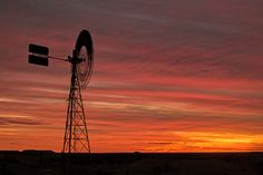 A silhouette of an Australian windmill at sunset. The windmill is an iconic sight throughout Outback Australia and much loved by photographers and artists. Windmills are an important part of rural life, and are used to draw water from bores and wells.