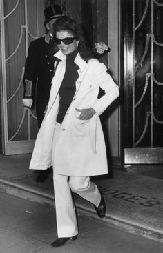 Jackie leaving Claridge's Hotel in London- trademark oversize shades &  a single-breasted mac style coat over flared hipster trousers w/polo neck jersey. (1970)