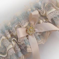 Vintage lace layers bridal garter... first, gold lace with a delicate blue shimmering pale gold overlay, then a nude Nottingham lace and finally an organza ribbon, all gathered together into a decadent ruffle!A luxury gold bow and flower crystal complete this garter.An ivory and blue bersion is now available with a silver crystal, select your favorite from the choices belowAll sizes availableNote: The new gold crystal now being used, is shown in the photo of the garter and horseshoe set…