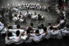"""Men perform the traditional Bulgarian """"Horo"""" dance in the icy waters of the Tundzha River in Kalofer as part of the Epiphany Day celebrations on January 6, 2012. (Dimitar Dilkoff/AFP/Getty Images) #"""