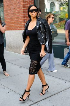 Kim Kardashian slouches a leather jacket over her shoulders for a cool + casual look in NYC