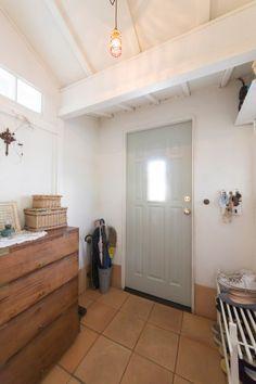 玄関ドアはアンティーク調のものを取りつけた。素朴な味わいの靴箱は和ものの骨董屋で購入。
