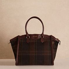 LARGE WOOL TRAVELER BAG $2750.00 A classic menswear-inspired plaid is reimagined for the modern woman in this brown-and-black wool bag. Supple Italian calfskin trim and gold-toned hardware highlight the style's clean, curved silhouette.