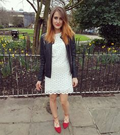Girl in white summer dress, red flat shoes and black leather jacket. Stylish outfit that goes perfectly with blonde ombre hair, red lipstick and matching red nails.