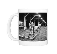 Golf By Night Golf By Night A golf instructor showing a young boy the rudiments of the game at the floodlit Paramatta Golf Range near Sydney, Australia. Photo Mug $29.99