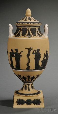 Wedgwood Yellow Jasper Dip Vase and Cover, England, c. 1930, upturned white handles, black classical figures in relief within a variety of foliate frames.